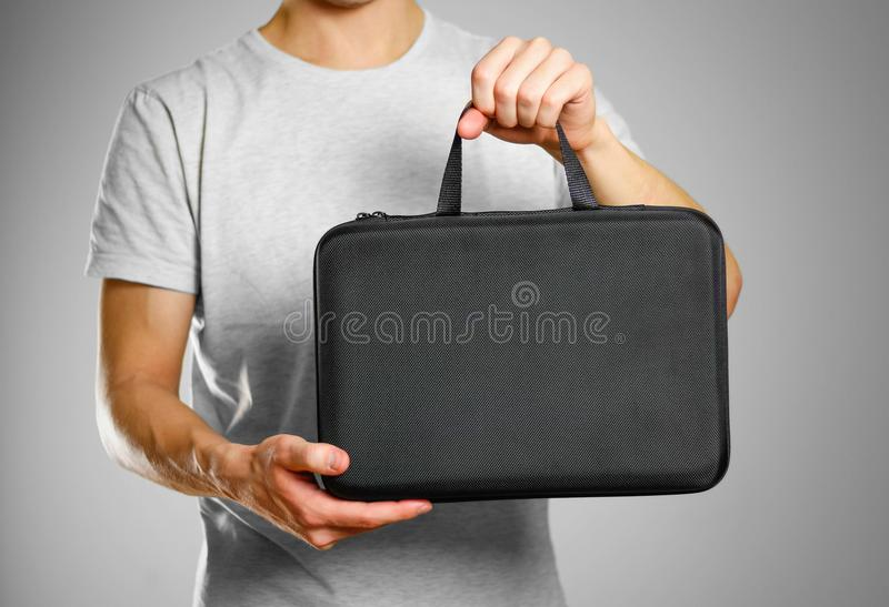 Un uomo in una maglietta grigia tiene una cassa nera Isolato sul BAC grigio fotografie stock libere da diritti