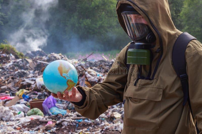 Un uomo in una maschera antigas esamina quando il bello pianeta Terra Sui precedenti di rifiuti di plastica brucianti Il concetto fotografia stock