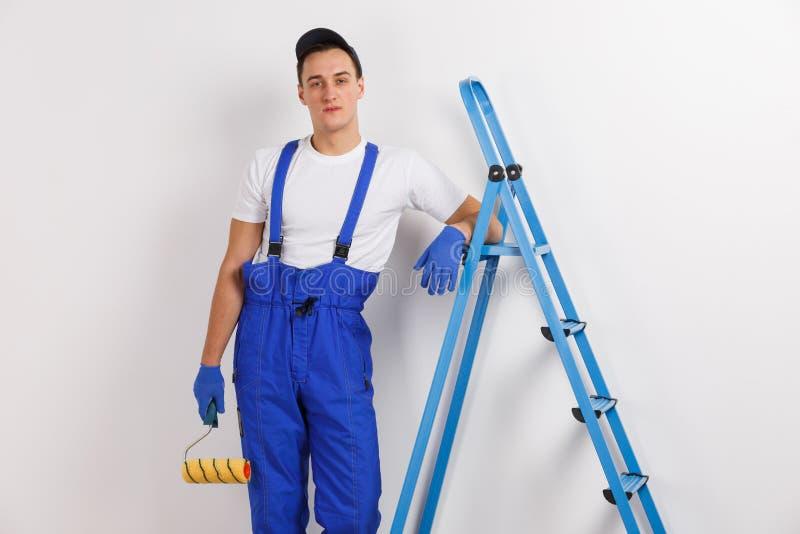 Un uomo, in un'uniforme blu, pendente il suo sgomita su una scala, tenente un rullo della costruzione fotografie stock