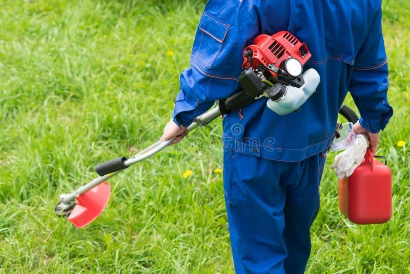 Un uomo in un'uniforme con una falciatrice da giardino sta andando tagliare l'erba verde immagini stock