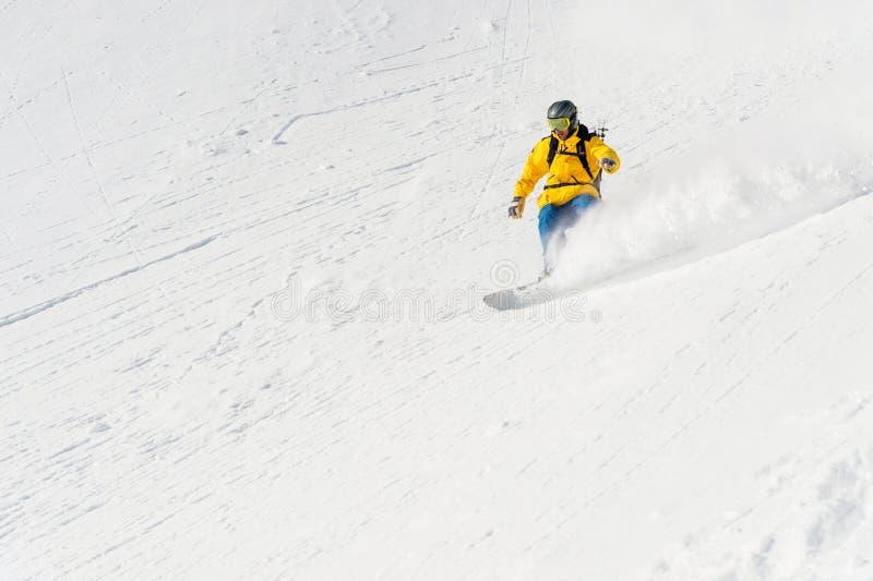 Un uomo uno snowboarder freerider discende un remoto all'alta velocità da un pendio fotografia stock libera da diritti