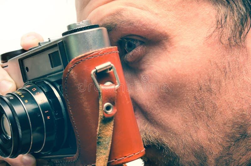 Un uomo usa una vecchia macchina fotografica immagine stock