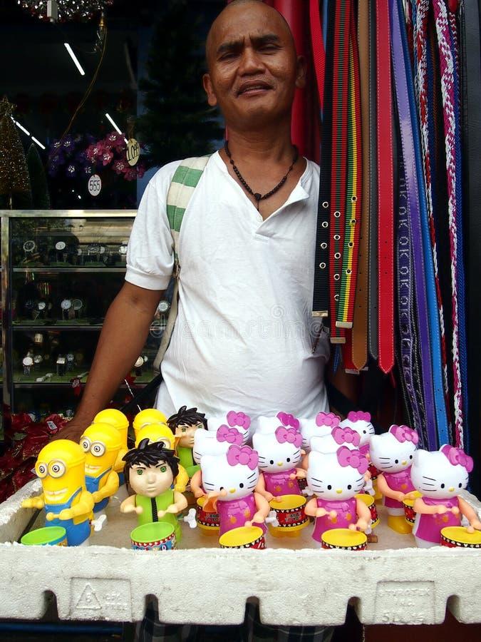 Un uomo vende il genere differente di giocattoli ad un marciapiede immagini stock
