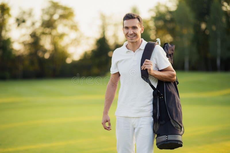 Un uomo in un vestito bianco cammina intorno al campo da golf con una borsa di club di golf e sorride fotografie stock
