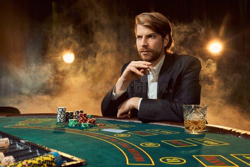 Un uomo in un vestito che si siede alla tavola del gioco Giocatore maschio Passione, carte, chip, alcool, dado, giocante, casinò fotografia stock