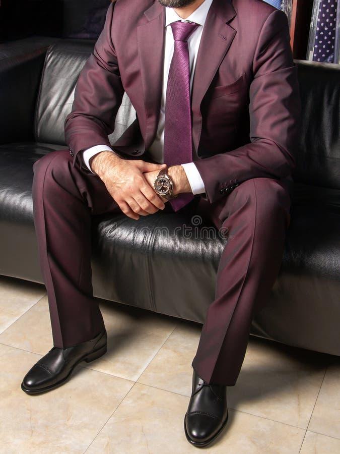 Un uomo in un vestito classico sta sedendosi su un sofà di cuoio nero, vista laterale di destra fotografia stock