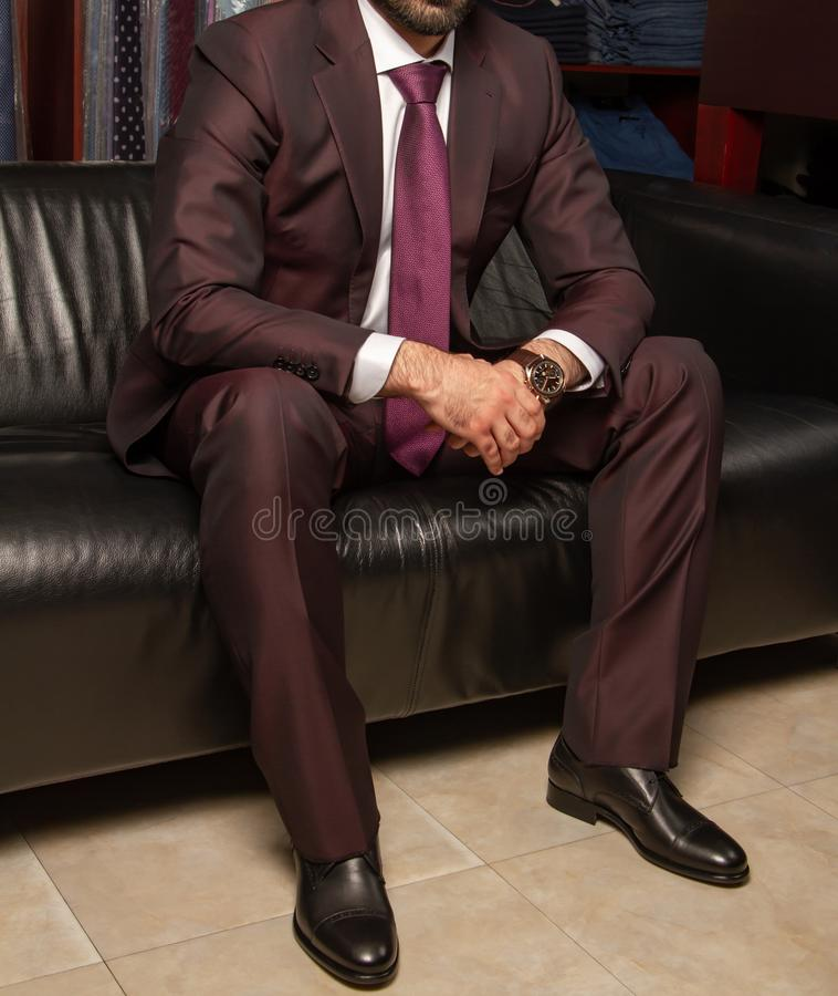 Un uomo in un vestito classico sta sedendosi su un sofà di cuoio nero, vista di parte di sinistra fotografie stock