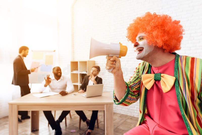Un uomo in un vestito del pagliaccio parla in un altoparlante fotografia stock