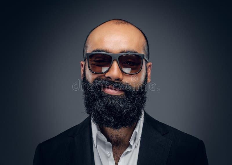 Un uomo in un vestito ed occhiali da sole su fondo grigio immagine stock