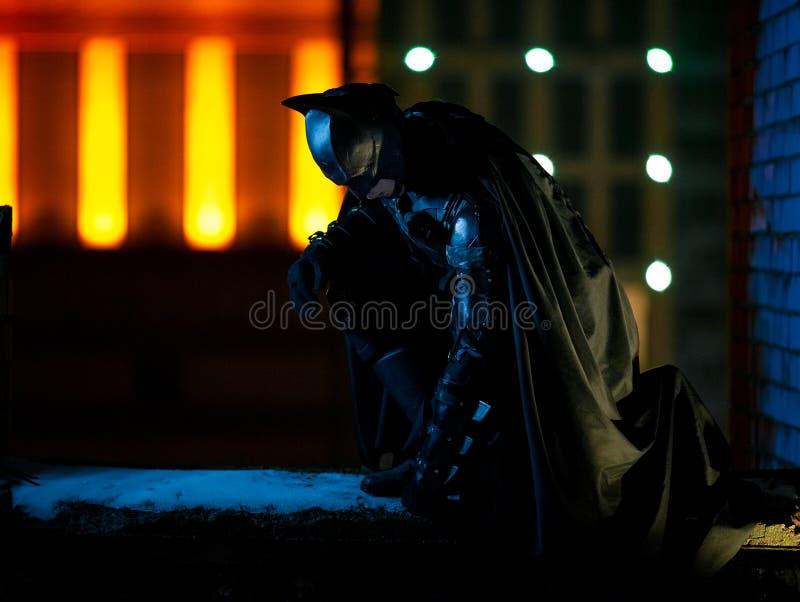 Un uomo vestito in maschera, armatura e mantello si siede contro lo sfondo delle luci della città di notte immagine stock libera da diritti
