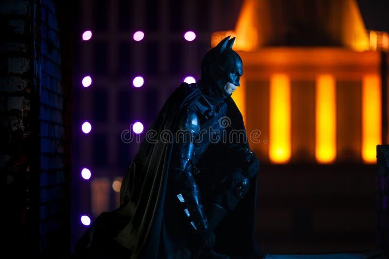 Un uomo vestito in maschera, armatura e mantello si siede contro lo sfondo delle luci della città di notte immagini stock libere da diritti