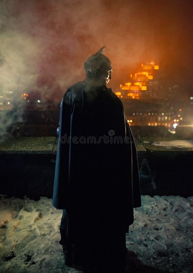 Un uomo vestito nei supporti del mantello e del casco contro lo sfondo delle luci e del fumo della città di notte fotografia stock libera da diritti