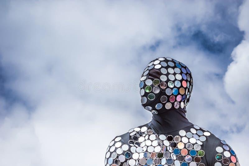 Un uomo in un vestito nero con una maschera decorata con i piccoli specchi rotondi fotografia stock