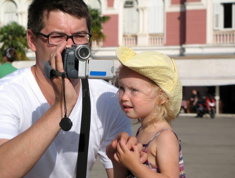 Un uomo in vetri e una bambina in un cappello giallo stanno registrando Giorno di estate caldo soleggiato immagine stock