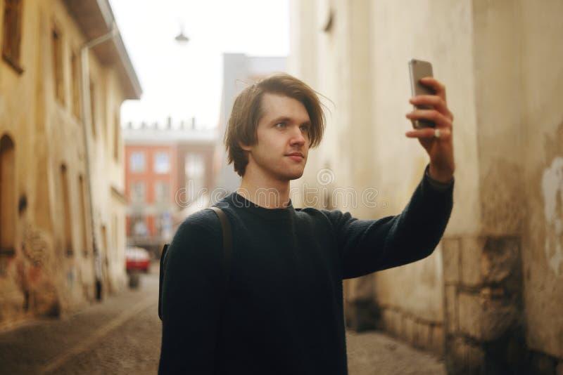 Un uomo viaggia in via di Europa Un uomo sorride, cammina tramite le vie di vecchia città, con una cartella Viaggi dello studente fotografia stock