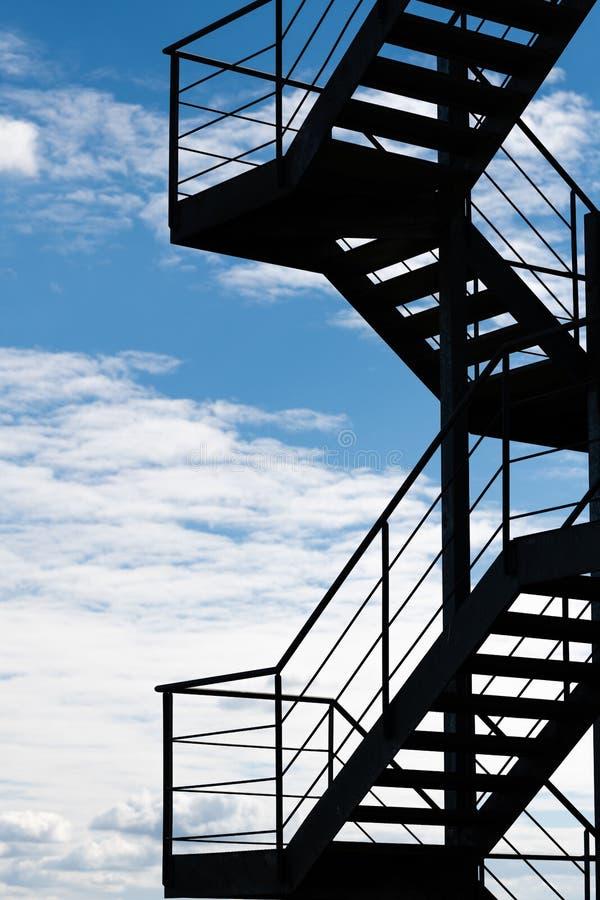 Un'uscita di sicurezza o una scala esterna su una costruzione profilata su un cielo luminoso immagini stock libere da diritti