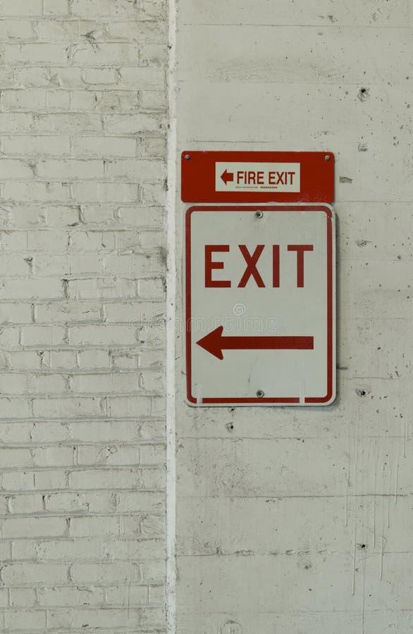 Un'uscita e l'uscita di sicurezza firmano in un parcheggio immagine stock