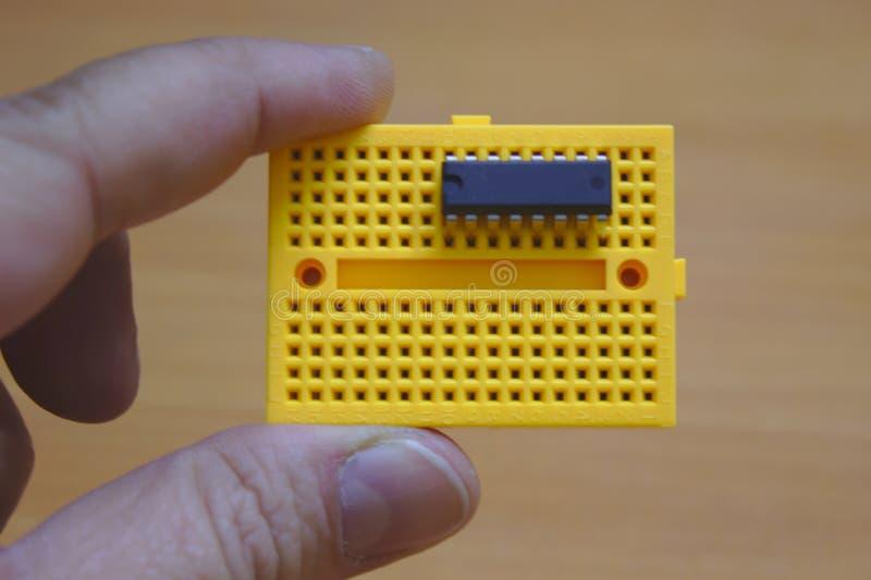 Un utente che giudica un protoboard giallo orizzontalmente con un CI montato immagine stock