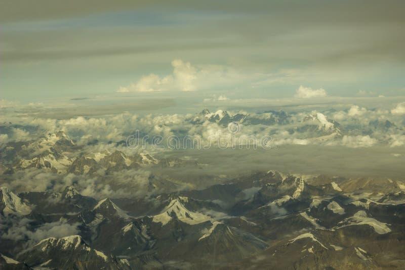Un valle gris de la montaña del desierto con las montañas y los picos nevosos debajo de las nubes blancas de una gran altura fotos de archivo libres de regalías