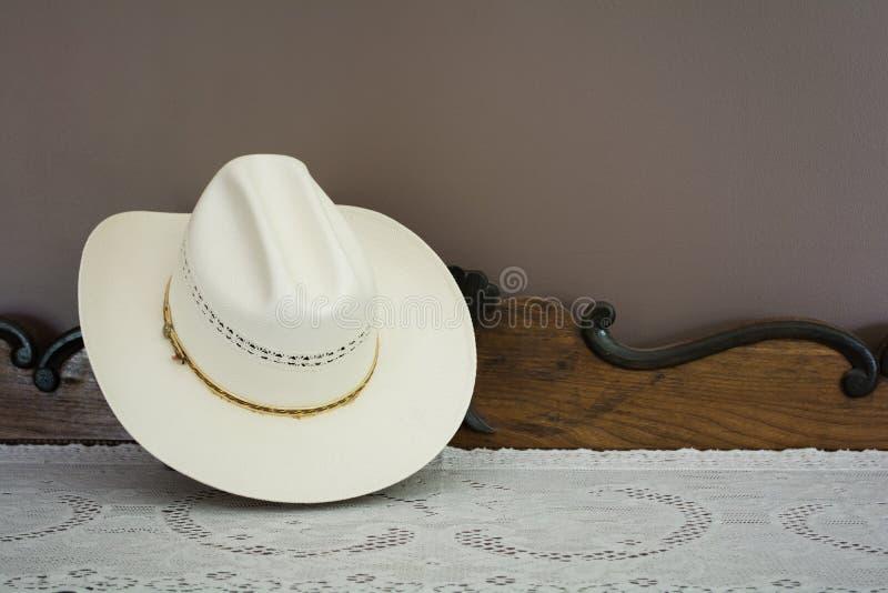 Un vaquero blanco Hat en un gabinete antiguo foto de archivo
