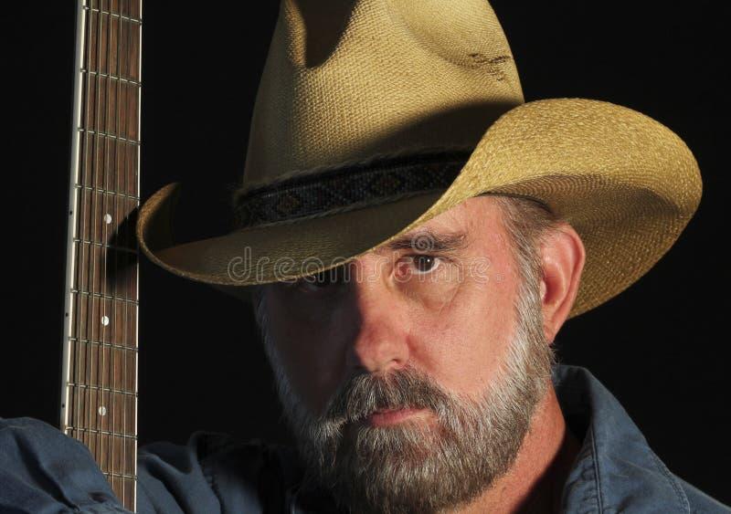 Un vaquero con una barba gris y una guitarra fotografía de archivo libre de regalías