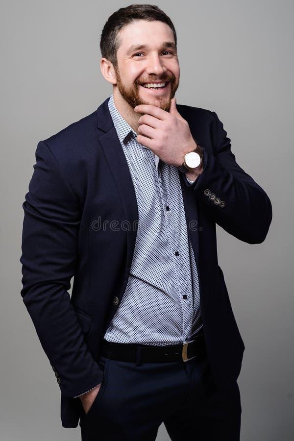 Un varón adulto en sus años 40 tempranos con una barba llena que lleva una chaqueta y una camisa imagen de archivo libre de regalías