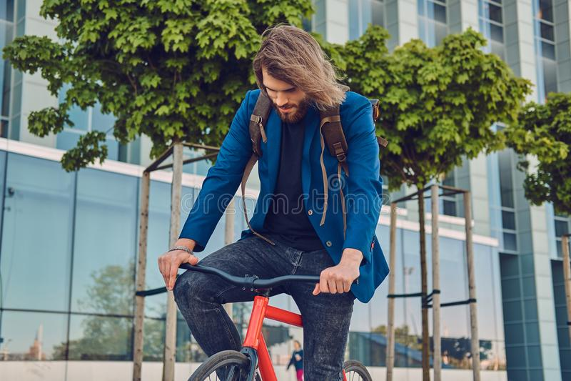 Un varón barbudo hermoso con el pelo largo en ropa y gafas de sol elegantes con una mochila, montando una bicicleta en la calle foto de archivo libre de regalías