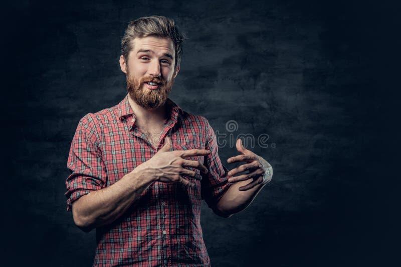 Un varón barbudo positivo vestido en una camisa roja del paño grueso y suave cuenta una historia con el movimiento de la mano fotografía de archivo