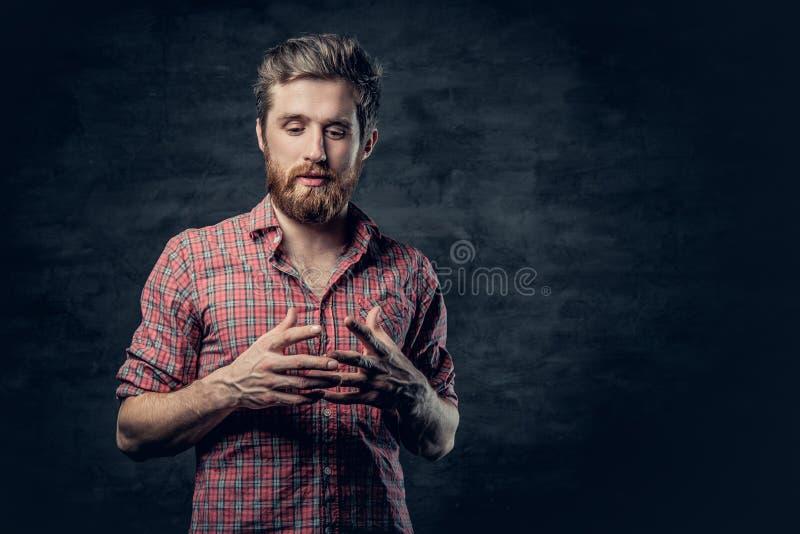 Un varón barbudo positivo vestido en una camisa roja del paño grueso y suave cuenta una historia con el movimiento de la mano imagen de archivo