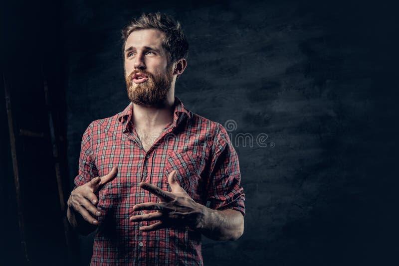 Un varón barbudo positivo vestido en una camisa roja del paño grueso y suave cuenta una historia con el movimiento de la mano imagen de archivo libre de regalías