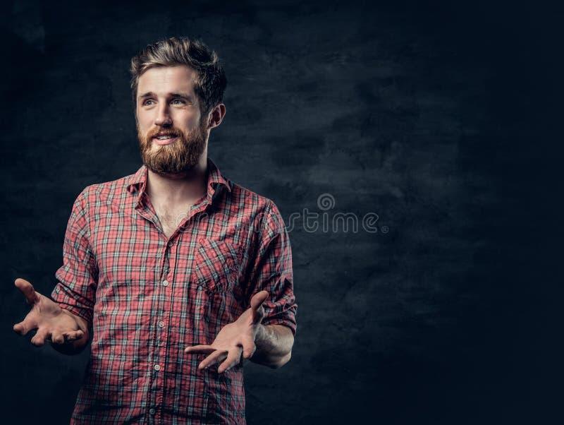 Un varón barbudo positivo vestido en una camisa roja del paño grueso y suave cuenta una historia con el movimiento de la mano imágenes de archivo libres de regalías
