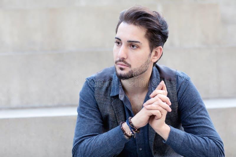 Un varón de moda pensativo joven que se sienta en el bleache concreto fotos de archivo