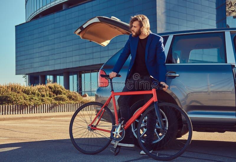 Un varón elegante barbudo con el pelo largo, colocándose con una bicicleta cerca del coche con un tronco abierto fotos de archivo libres de regalías