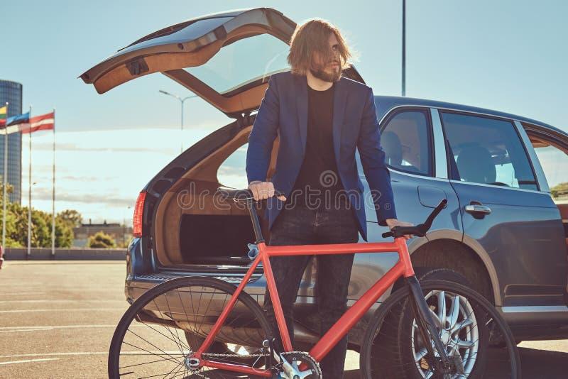 Un varón elegante barbudo con el pelo largo, colocándose con una bicicleta cerca del coche con un tronco abierto foto de archivo