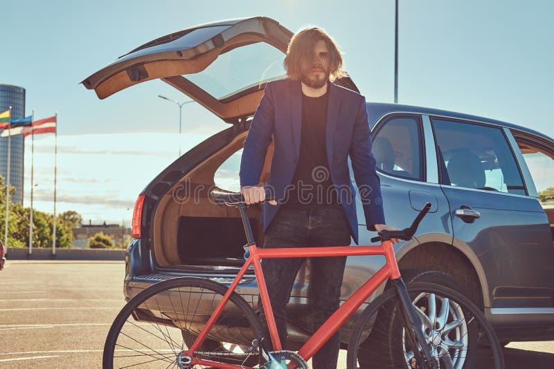 Un varón elegante barbudo con el pelo largo, colocándose con una bicicleta cerca del coche con un tronco abierto fotografía de archivo libre de regalías