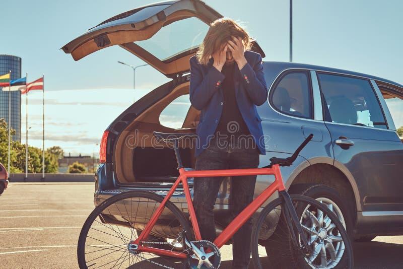 Un varón elegante barbudo con el pelo largo, colocándose con una bicicleta cerca del coche con un tronco abierto imagen de archivo