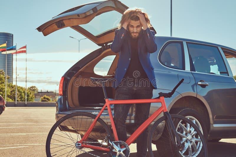 Un varón elegante barbudo con el pelo largo, colocándose con una bicicleta cerca del coche con un tronco abierto foto de archivo libre de regalías