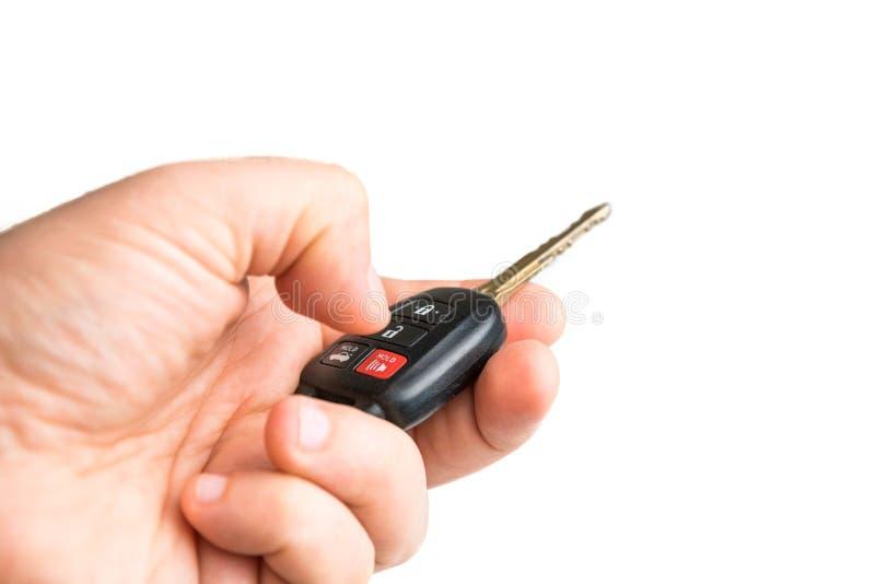 Un varón está llevando a cabo una llave del coche en su mano y está presionando el botón de la alarma Cierre para arriba foto de archivo libre de regalías