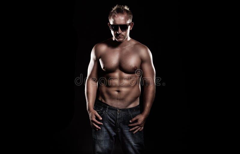 Un varón joven muy cabido que dobla sus músculos fotos de archivo libres de regalías