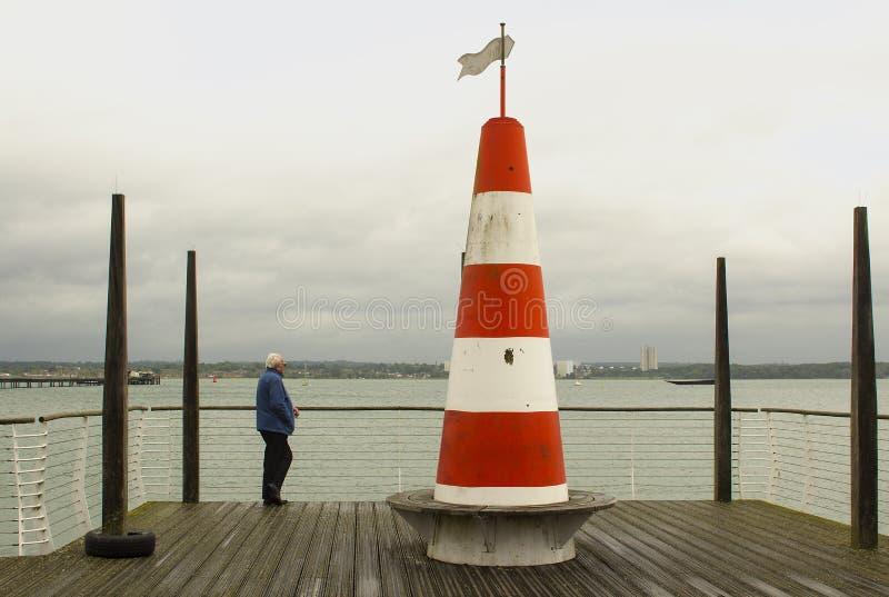 Un varón solitario en el embarcadero de la plataforma de la visión que pasa por alto el agua ocupada de Southampton en Hythe en H fotos de archivo libres de regalías