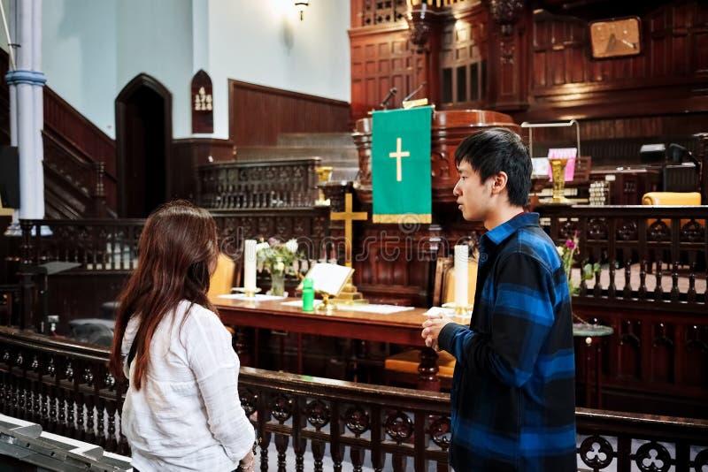 Un varón y una persona femenina que tienen una conversación religiosa delante del altar del St James United Church en Montreal, Q fotos de archivo