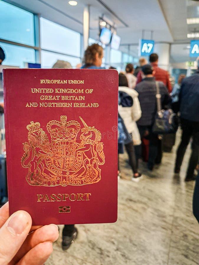 Un var?n blanco sostiene su pasaporte brit?nico rojo en su mano en el medio de un terminal apretado de la salida imágenes de archivo libres de regalías