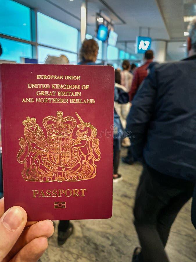 Un var?n blanco sostiene su pasaporte brit?nico rojo en su mano en el medio de un terminal apretado de la salida fotos de archivo libres de regalías