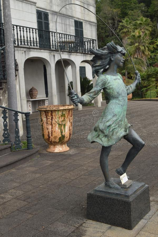 Un vase orange contrairement au coppergreen d'une statue photographie stock libre de droits