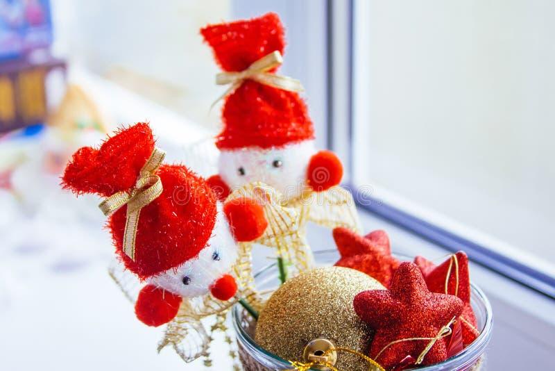 Un vase se tient à la fenêtre a rempli de jouets rouges et jaunes d'arbre de Noël Deux bonhommes de neige sur des bâtons sont sur image libre de droits