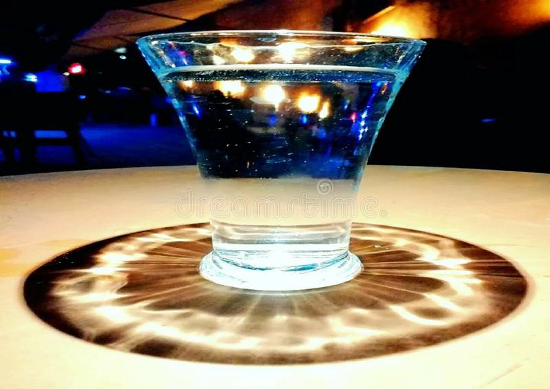 Un vaso de agua en el centro de las luces imágenes de archivo libres de regalías