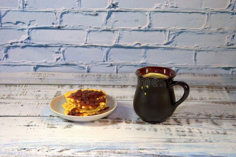 Un vaso de cerámica marrón con té caliente y un plato de gofres con mermelada de fresa imágenes de archivo libres de regalías