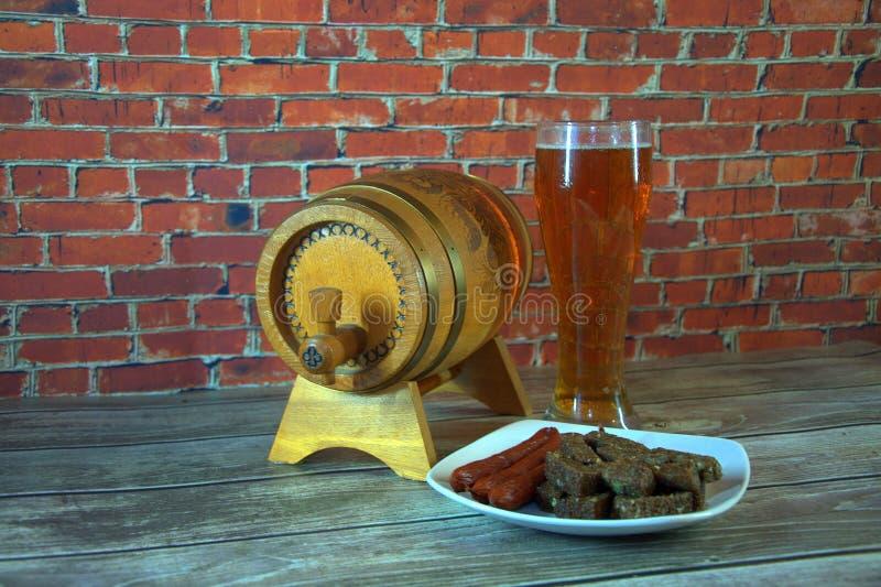 Un vaso de cerveza, un barril de madera y una placa de bocados están en la tabla al lado de la pared Primer foto de archivo