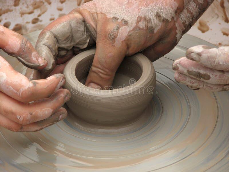 Un vaso di argilla su una ruota delle terraglie con la fabbricazione passa fotografia stock libera da diritti