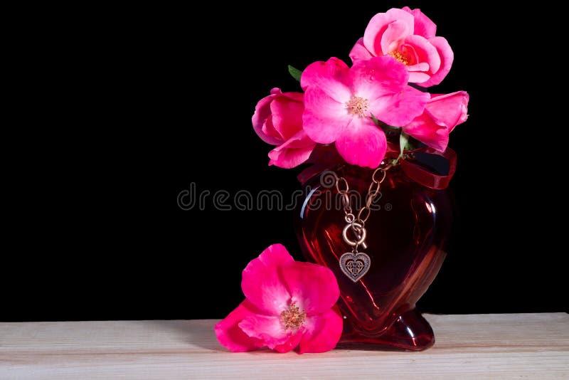 Un vaso rosso del cuore con una bella collana del cuore e le rose rosa fotografia stock libera da diritti